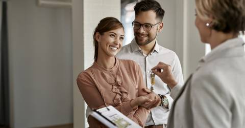 Jong gelukkig paar dat sleutels van hun nieuw huis van makelaar ontvangt
